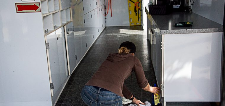 After sweeping out the sand and drit from the trailer, the floors are wiped clean - West Orange County CERT Trailer Team